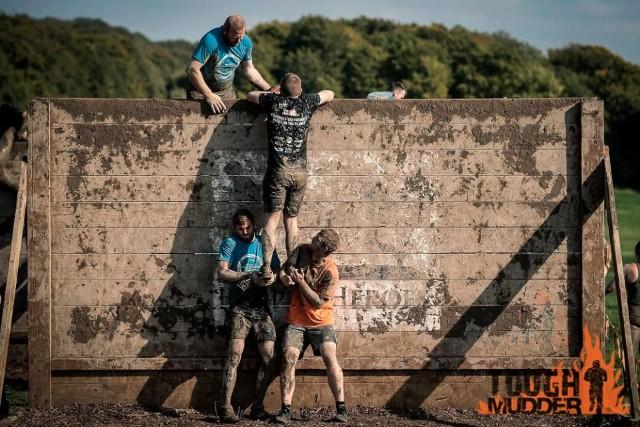 Mudders tackle a Hero Wall.
